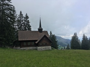 Small wooden chappel on top of an alpine meadow