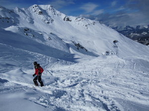 Off-piste above Meribel (Andy standing on skis, in front of mountains)