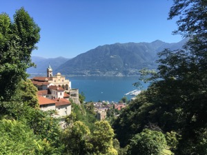 View over church Santuario della Madonna del Sasso, framed by trees with the lake in the background