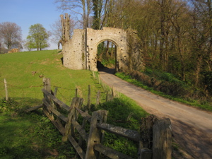 Ruined stone gate (New Gate at Winchelsea) over road, surrounded by fields and trees