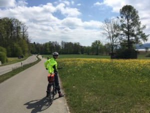Jules in a bright yellow cycling vest, next to a field
