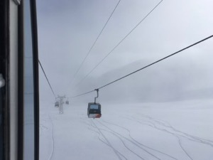 View of foggy ski slope from inside cable car