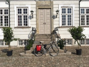 Bicycle with red panniers leaning against the steps to a house.