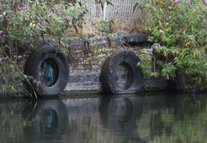 Old Tyres hanging along the side of a canal wall