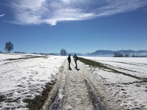 Two figures in silhouette on a snowy path under blue skies, with mountains in the background.