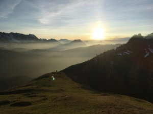 View along the alps, with the sun setting and clouds creeping through the valleys