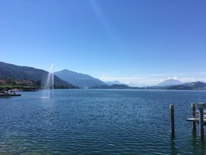 Fountain and blue waters of the Zuggersee, under blue skies, Rigi and Pilatus mountains in the background