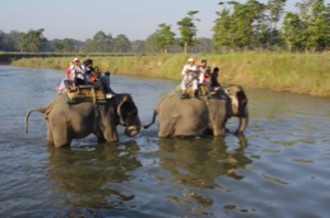 People on elephant back crossing a river